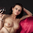 Nude woman on a satin bedenjoying a glass of red wine — Stock Photo #4213378