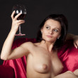 Nude woman on a satin bed enjoying a glass of red wine — Stock Photo #4213390