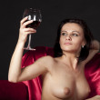 Stock Photo: Nude woman on a satin bed enjoying a glass of red wine